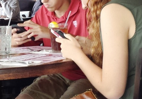 Two teenagers on cellphones