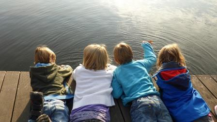 Kids enjoy sunny day lying on dock