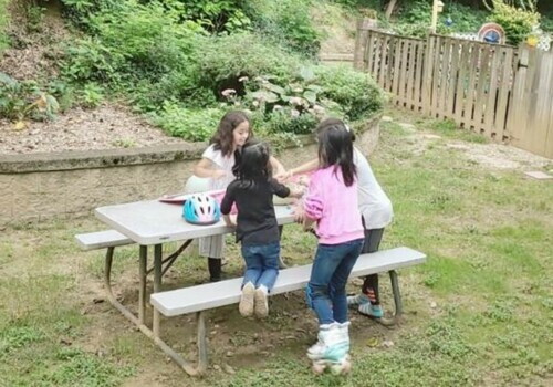 Four children take a break from school by playing together outdoors